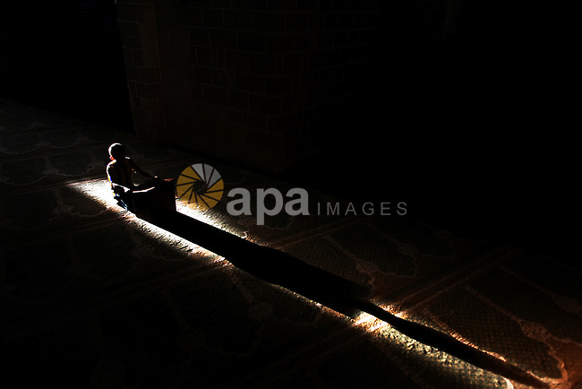 A Palestinian boy reads Quran at a Mosque in Gaza City on the third day of the Muslim fasting month of Ramadan, on July 1, 2014. Muslims around the world celebrate Ramadan, the holiest month in the Islamic calendar, in which they abstain from eating, drinking and conducting sexual relations from sunrise to sunset. Photo by Ali Jadallah