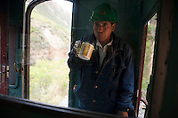 A train employee has breakfast at the last car of the train. For safety, there is always a worker in the last car.