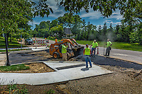 Asphalt workers install new entrances to side streets off Hempstead Rd. where the city built a new bike and walk path.