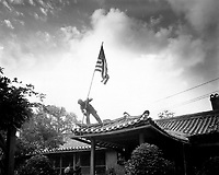 Marine Pvt. 1st Class Luther Leguire raises U.S. Flag at American consulate in Seoul, while fighting for the city raged around the compound.  September 27, 1950.  Sgt. John Babyak, Jr. (Marine Corps)<br /> NARA FILE #:  127-N-A3386<br /> WAR &amp; CONFLICT BOOK #:  1424
