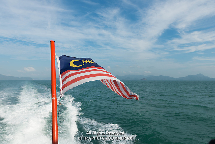 Flag of Malaysia on jetti speedboat with Andaman sea behind, Langkawi