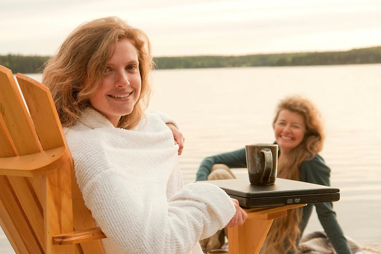 Two women sitting on a dock in the early morning having coffee looking at the camera.  Computer sitting on the arm of the chair, lake in background.<br /> Clear Lake Manitoba, Canada