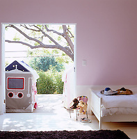 The pink children's bedroom has French windows that open onto a sunny deck complete with play tent