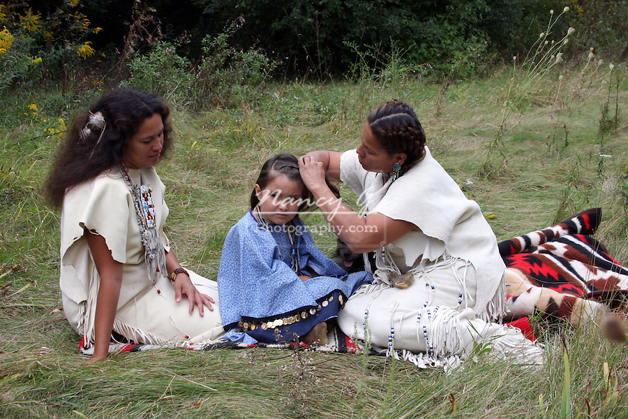 A group of Native American Lakota Sioux Indian women sitting on a blanket braiding the hair of a child