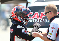 Jun 6, 2016; Epping , NH, USA; NHRA top fuel driver Steve Torrence is helped with safety gear by a crew member during the New England Nationals at New England Dragway. Mandatory Credit: Mark J. Rebilas-USA TODAY Sports