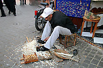 North Africa, Africa, Morocco, Marrakesh. Traditional woodcarver makes chess pieces on the street in Marrakesh.