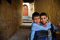 Two kids playing on their way back from school in the old medina of Fes, Morocco