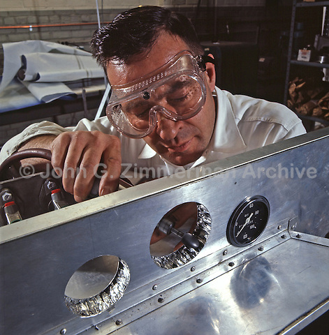Ford engineer adjusts holes for dashboard instruments on a racing-car chassis made of honeycomb aluminum. Ford Motor Company, Dearborn Michigan, 1966. Photo by John G. Zimmerman.