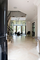 A two storey atrium style entrance hallway features a Bocci pendant chandelier which hangs down above spanning two floors. Immediately ahead is the formal dining room which can comfortably seat ten.