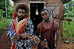 Acasekam Saint Jerar (left) is a voodoo priest in Mizak, a small village in the south of Haiti. He is standing in front of a small room he uses for ceremonies. On the right is his assistant, Pouchon Frederique.