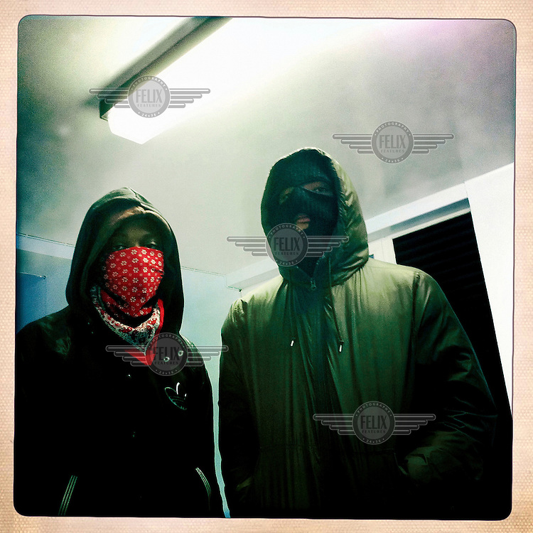 Two youths, their faces covered to avoid identification, in Notting Hill, West London during an outbreak of civil disorder sparked by the death of Mark Duggan, who was shot and killed by the police during an attempted armed 'hard stop'. Peaceful protests against his death quickly escalated into rioting and widespread looting, gripping London and other major English cities for days.