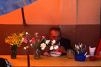 "Flowers decorate a lunch table in the local produce market in Vallegrande, Bolivia Sunday, Nov. 14, 2004. Ernesto ""Che"" Guevara was captured by the Bolivian army in 1967 in a nearby valley and executed in La Higuera days later. His body was put on public display in the laundry room of the Vallegrande hospital, then secretly buried under the air strip for 30 years. Guevara and fellow communist guerillas were attempting to launch a continent-wide revolution modeled on Guevara's success in Cuba in the late 1950s. The Bolivian government recently began promoting the area where he fought, was captured, killed and burried for 30 years as the ""Ruta del Che,"" or Che's Route. (Kevin Moloney for the New York Times)"