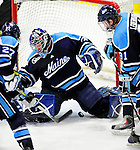 30 January 2010: University of Maine Black Bears' goaltender Scott Darling, a Sophomore from Lemont, IL, with the puck trickling between his legs, manages a save against the University of Vermont Catamounts at Gutterson Fieldhouse in Burlington, Vermont. The Black Bears and the Catamounts played to a 4-4 tie in the second game of their America East weekend series. Mandatory Credit: Ed Wolfstein Photo