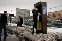 A woman recharges her phone credit in the snow at a housing estate on the outskirts of Moscow. .Picture by Justin Jin.