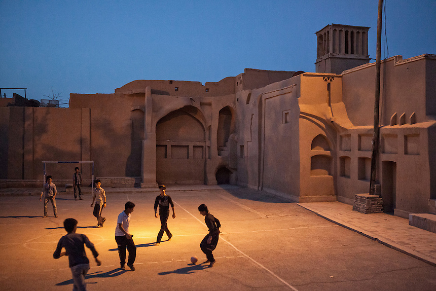 At dusk, the courtyard of a mud-brick building in the Yazd Old City serves as football field for local children. Located in the middle of the desert in Central Iran, Yazd is arguably one of the oldest living city in the world. Yazd was visited by Marco Polo in 1272, who described it as a good and noble city and remarked its silk production. The name Yazd means worship. And badgir, the wind tower to control the indoor temperature, is one of distinctive feature of this city (visible at the upper right corner of the photograph).