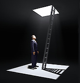 A man standing in a pit looking up to the ladder that leads out in to the light.