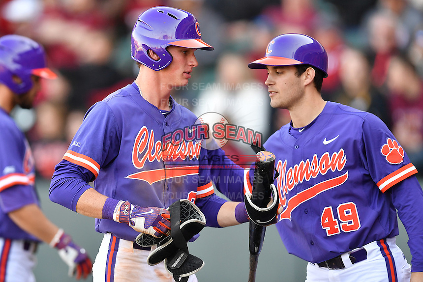 Shortstop Logan Davidson (8) of the Clemson Tigers is congratulated after scoring a run in the Reedy River Rivalry game against the South Carolina Gamecocks on Saturday, March 4, 2017, at Fluor Field at the West End in Greenville, South Carolina. Clemson won, 8-7. (Tom Priddy/Four Seam Images)