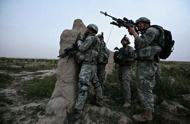 A soldier with Company A, 2nd Battalion, 2nd Infantry Regiment peers through the scope of a sniper rifle, trying to pinpoint Taliban fighters who have attacked a U.S. patrol near the village of Mira Hor in Kandahar province, Afghanistan. April 18, 2009. DREW BROWN/STARS AND STRIPES