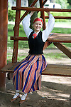 Young Smiling Woman in Estonian National Costume Sitting on Swing