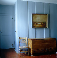 In the hall the patina and grain of an antique wooden chest echo the tones in the seascape hanging above