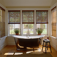 An elegant roll-top bath sits in an alcove surrounded by windows overlooking the walled garden