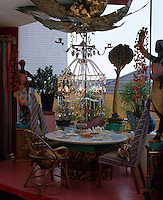 An elaborate chandelier hangs over a table surrounded by exotic wooden statues that is laid for afternoon tea