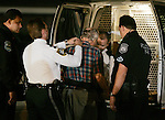 A supporter of Teri Schiavo (C) is patted down by a member of the Pinellas County Florida sheriffs department while being arrested for attempting to bring Terri Schiavo a bottle of water at the Woodside Hospice on March 23, 2005 in Pinellas Park, Florida. Three supports were arrested. REUTERS/Scott Audette