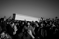 Tripoli, Libya, March 24, 2011.In this image taken during an organized trip by the Libyan authorities, men gather at a mass funeral for people killed in Coalition bombings, officials said. The cause of deaths as well as victims identities could not be verified. French fighter jets struck an air base deep inside Libya Thursday.