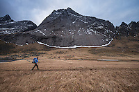 Mountain peak rises above female hiker hiking trail towards Horseid beach, Moskenesøy, Lofoten Islands, Norway