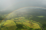 Aerial - rain falling and sun shining on the mainland sugarcane farmland creating a rainbow.