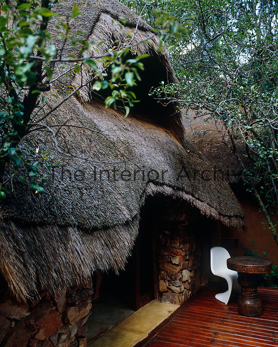A Verner Panton chair sits on the terrace below a great thatched roof which has great insulation properties