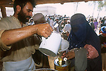 An Afghan woman refugee receives cooking oil during distribution of humanitarian aid at the Shamshatoo refugee camp..