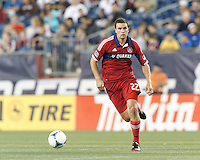 Chicago Fire defender Austin Berry (22) brings the ball forward.  In a Major League Soccer (MLS) match, the New England Revolution (blue) defeated Chicago Fire (red), 2-0, at Gillette Stadium on August 17, 2013.