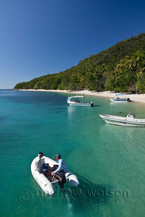 Men cruising in zodiac at Welcome Bay.  Fitzroy Island National Park, Cairns, Queensland, Austtralia