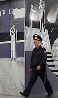 Moscow, Russia, 20/06/2010..A policeman walks past murals depicting Raskolnikov's double murder and Svidrigailov's suicide in Crime &amp; Punishment at the just-opened Dostoevsky metro station, the newest in Moscow's underground metro system. The station's opening was delayed by several weeks after psychiatrists claimed the gloomy and violent images in murals depicting scenes from Dostoevsky's novels would make the station a &quot;mecca for suicides&quot;.