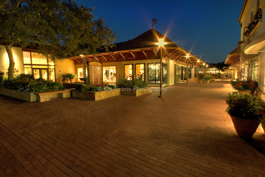 Shops lit up at night in the Carmel Plaza in Carmel, California.