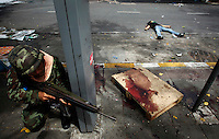 """ATTENTION EDITORS - VISUALS COVERAGE SCENES DEATH AND INJURY..A Thai army soldier crouches behind a street sign near the body of a protester who was killed during an operation to evict anti-government """"red shirt"""" protesters from their encampment in Bangkok May 19, 2010. Thai troops and armoured vehicles broke through barricades of tyres and staves on Wednesday in a fresh offensive to evict thousands of anti-government protesters from their fortified camp in central Bangkok, witnesses said.   REUTERS/Damir Sagolj   (THAILAND - Tags: POLITICS MILITARY CIVIL UNREST IMAGES OF THE DAY) TEMPLATE OUT"""