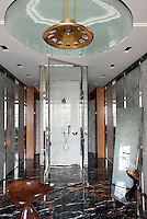 A glass and onyx shower cubicle sits on a dark marble floor in the centre of this glamorous bathroom