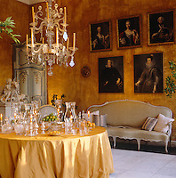 A series of 17th and 19th century portraits hangs on the wall of this yellow dining room and the table is filled with a collection of candlesticks and glass lanterns