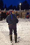 Man wearing traditional Sami hat at reindeer roundup at Vuomaselkä, Lapland, where semi-domesticated deer are sorted and seperated for breeding, slaughter, returned to their owners, injected for parasites, or released back into the forest.
