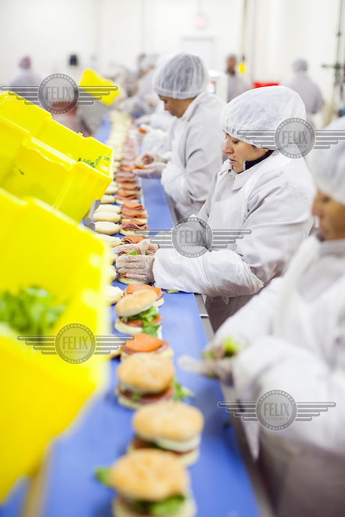 Workers, dressed in food hygiene workwear, assemble sandwich rolls, at Greencore's Newburyport facility, near Boston. Greencore Group is an Irish-based company that produces convenience foods and sandwiches throughout Britain and Europe. In 2008 Greencore acquired Home Made Brand Foods in Newburyport, Massachusetts to establish Greencore North America.