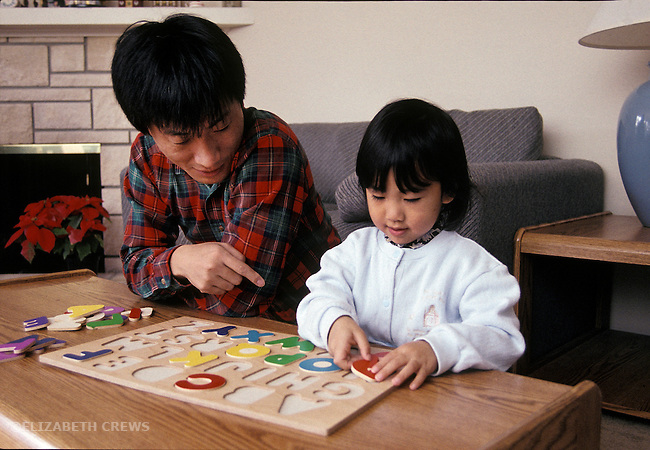 Palo Alto, CA Father giving daughter, three-years-old help in doing alphabet puzzle