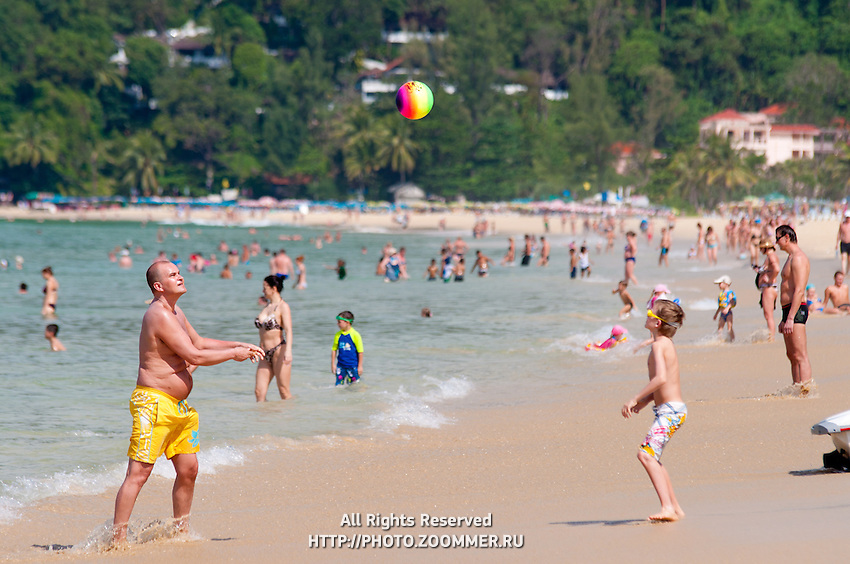 Father and son play ball on Karon beach in Phuket, Thailand
