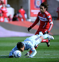 Sporting KC defender Roger Espinoza (15) sends a diving header back to his goalkeeper in front of Chicago Fire forward Gaston Puerari (18).  The Chicago Fire defeated Sporting KC 3-2 at Toyota Park in Bridgeview, IL on March 27, 2011.