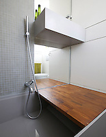 In the bathroom there is a pull-down section of floor giving access to the wash basin when the bath is not in use and is also used as a bench for showering