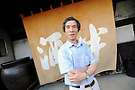 """Yasutaka Daimon, president and owner of Daimon Sake Brewery Co., stands by the """"noren"""" curtain at the entranceway to his brewery in Osaka, Japan on July 24 2008. Daimon is the 6th generation master brewer at Sakahan, which has been in existence for the best part of two centuries. Sakahan is a key exporter of sake, a wine-like alcoholic beverage fermented from rice, particularly to the U.S. where his popular Mukune brand is available in 44 states..Photographer: Robert Gilhooly"""
