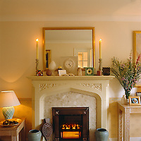Detail of a fireplace with a simple surround and painted mantelpiece