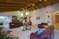 Large traditional livingroom with tongue-in-groove wooden ceiling, leather couches in Spanish style home