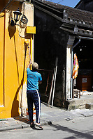 Painters at work in Hoi An, January 18, 2017 few days after flooding in the city.