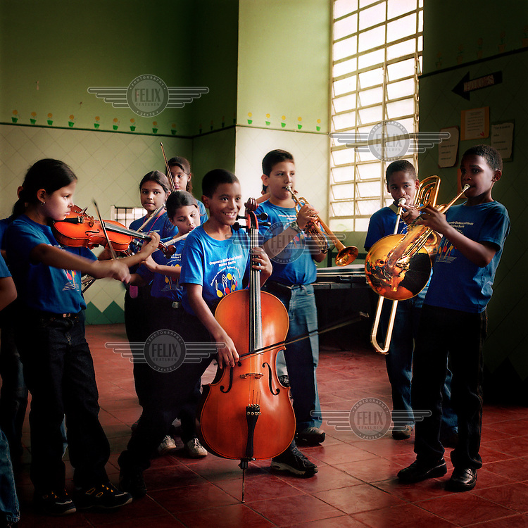 Children rehearsing at a school in the impoverished neighbourhood of Sarria. 275,000 pupils, most of them under 18, take part in Maestro Jose Antonio Abreu's 'El Sistema'. It was dreamed up in 1975, in his own basement, and has been exported to 23 countries. 85 percent of the students involved come from the poorest areas of Venezuela, and for many it has proved to be a personal salvation, proving to themselves and their communities that music can play a huge role in alleviating the strains of poverty.